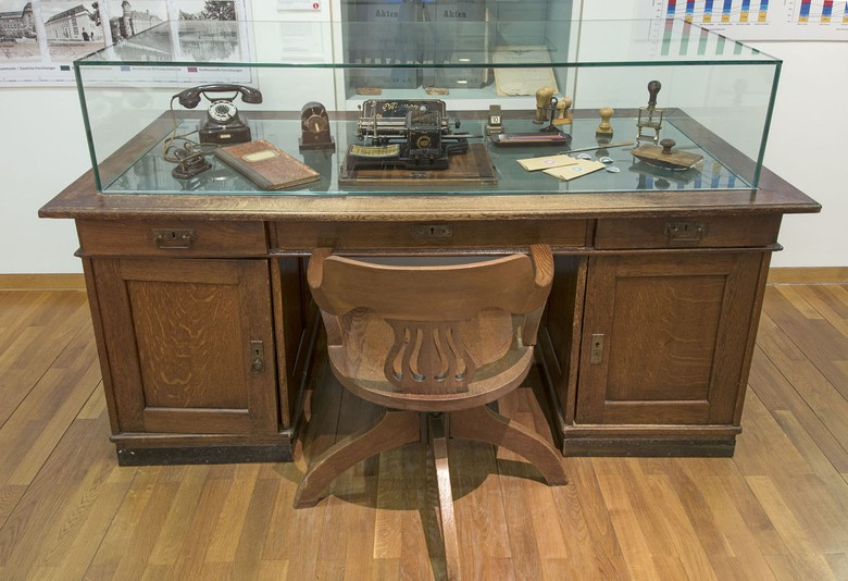 "The photo shows a desk in display cabinet 25 of the Stadtmuseum Münster. The desk symbolises the development of Münster in the 19th century to become an administration town – thus the description of Münster as the ""desk of Westphalia""."